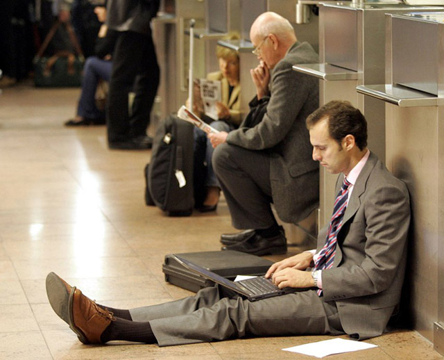A businessman works with his laptop at a check-in counter as he has to wait at Brussels' Zaventem International Airport, Thursday April 27, 2006. Authorities reopened a busy terminal at Brussels' Zaventem International Airport, Thursday, after a man who was behaving suspiciously had fled into the zone. All flights from the terminal were immediately suspended and passengers were told to leave the terminal while police searched for the man. (AP Photo/Yves Logghe)